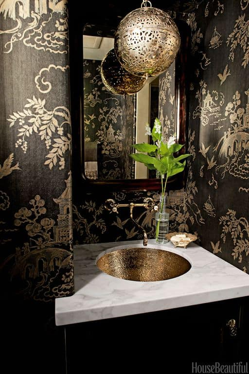 Traditional black powder room with complex marble counters and interior wallpaper.