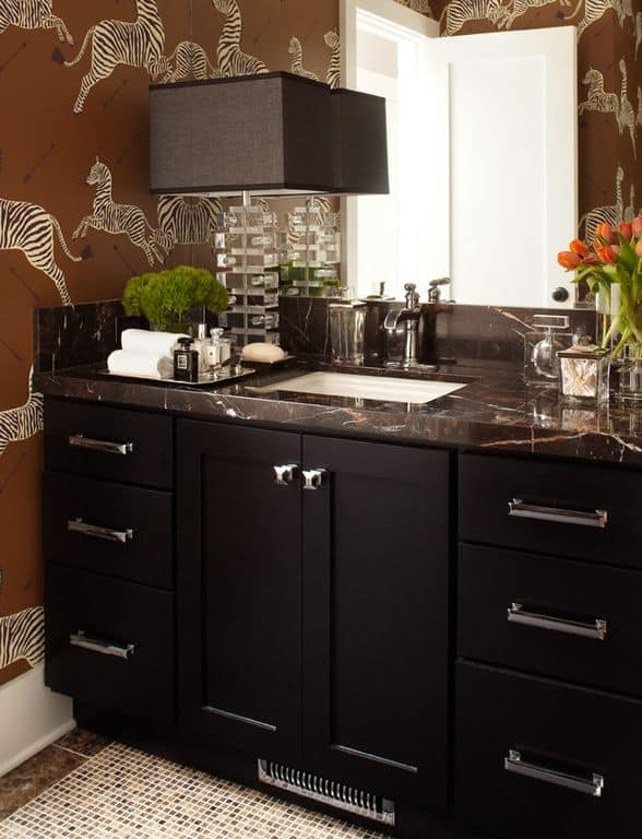 Black powder room with interior wallpaper and specialty door.