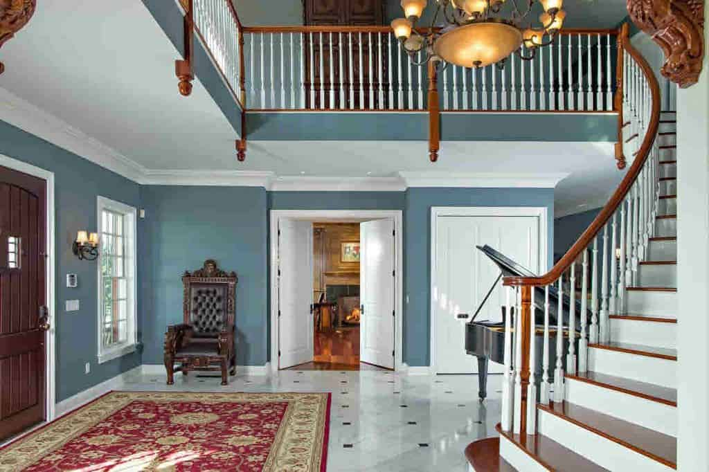 This stylish foyer features a classy rug and ceiling light. The chair on the corner looks enchanting.