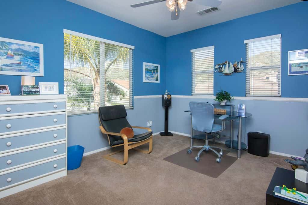 eclectic home office with ceiling fan light blue walls and carpet flooringsource zillow digs