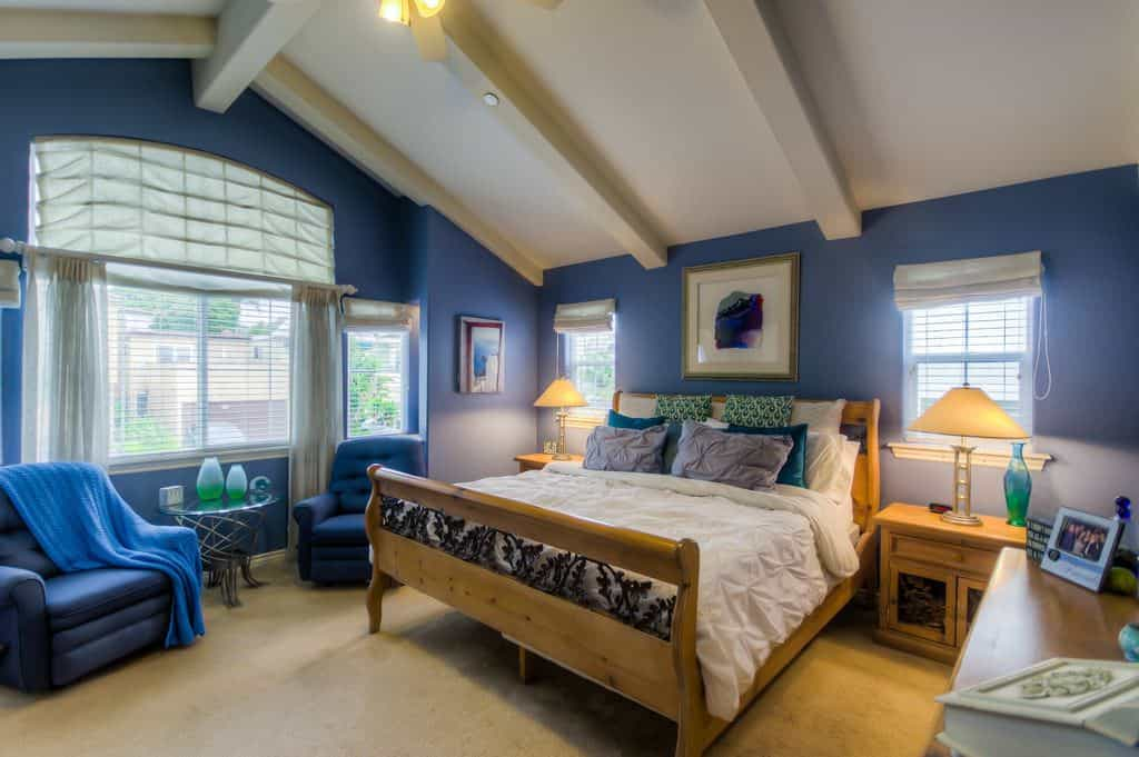 Cottage style primary bedroom with beam ceiling, blue walls and beige carpet flooring.
