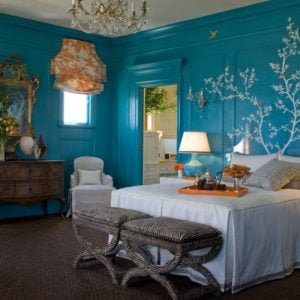 Eclectic blue primary bedroom with wall mural, orange draperies and carpet flooring.