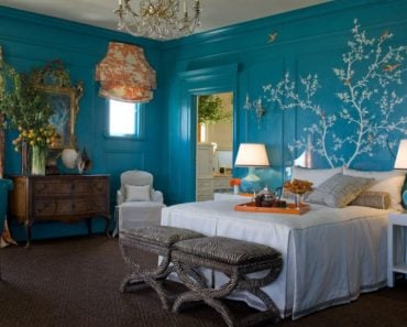 Eclectic blue master bedroom with wall mural, orange draperies and carpet flooring.