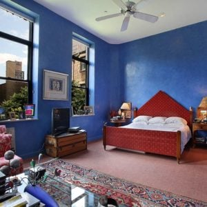 Large Eclectic primary bedroom that creates a three-piece visual layers from the shed ceiling, deep blue walls and rustic carpet flooring.