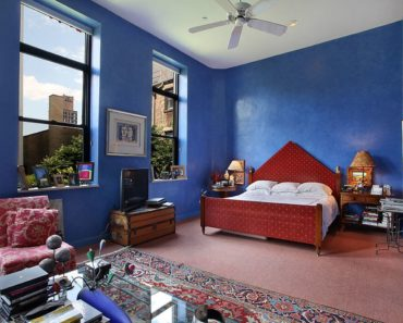Large Eclectic master bedroom that creates a three-piece visual layers from the shed ceiling, deep blue walls and rustic carpet flooring.
