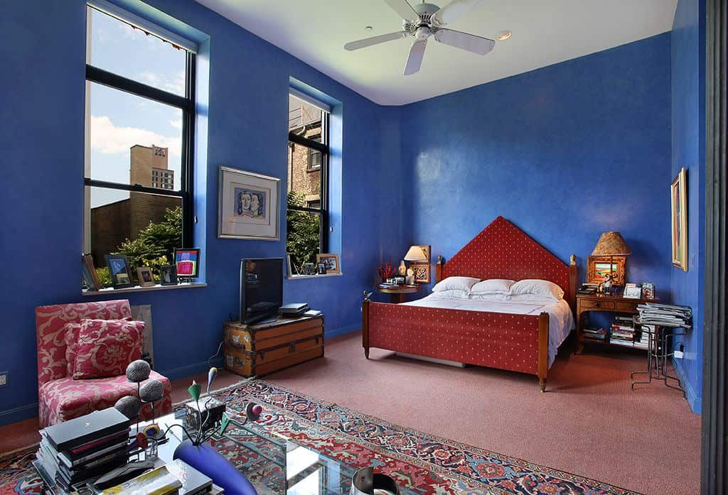 This blue primary bedroom is beautifully contrasted with a red dotted bed and a patterned chair facing the glass top coffee table over a classic rug. It has carpet flooring and vibrant blue walls adorned by lovely artworks.