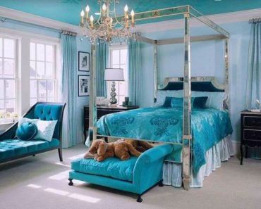 This eclectic master bedroom makes the chandelier and four poster bed frame sparkle against the blue backdrop.