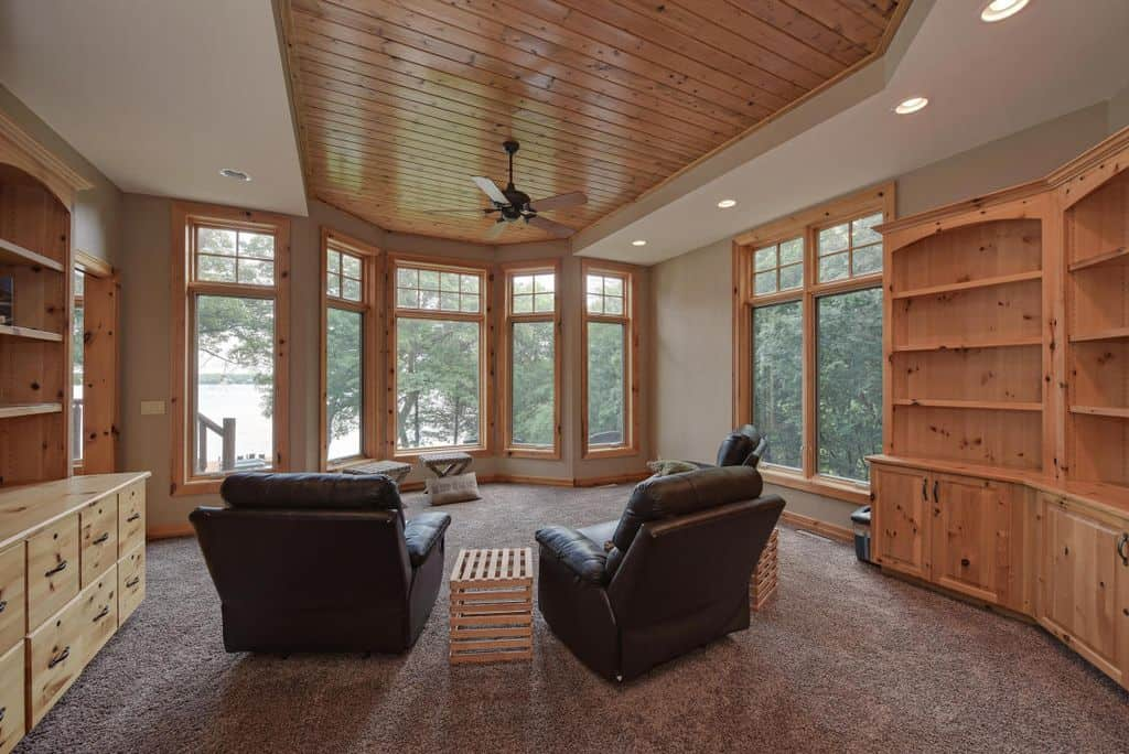 This room boasts multiple shelving and cabinetry along with comfy seats set on the carpet flooring.