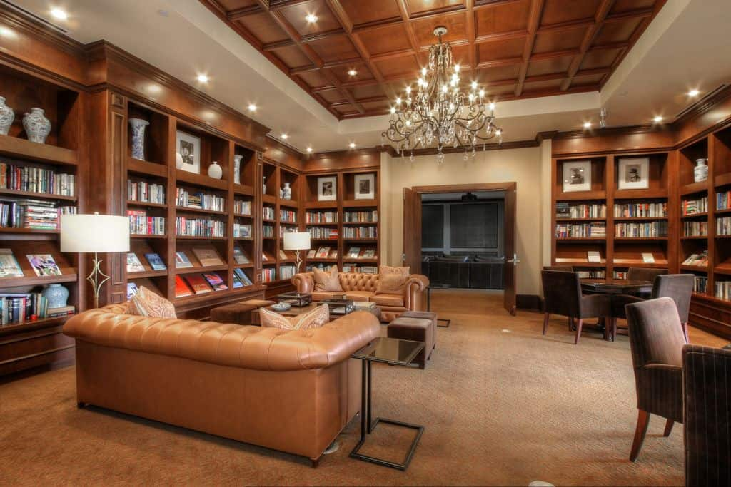 Warm living room surrounded with built-in bookshelves that are lighted by recessed lights and a grand chandelier that hung from the wooden coffered ceiling.