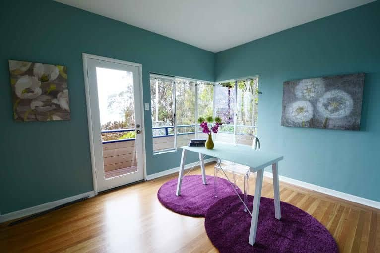A charming home office decorated with lovely floral wall arts mounted on the blue walls. It has a white office desk and glass chair that sit on purple round rugs over hardwood flooring.