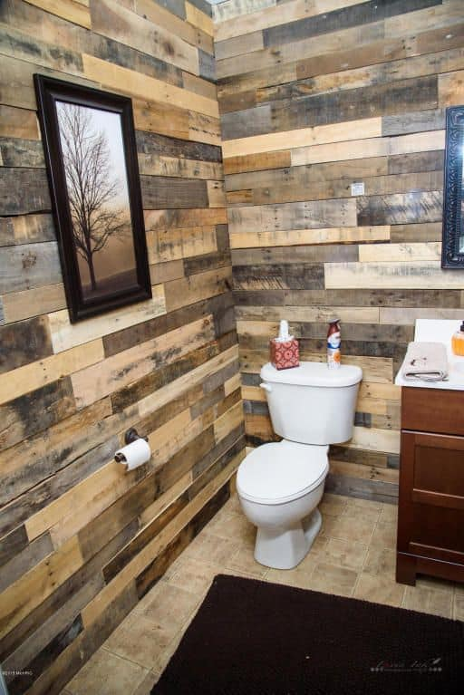 Farmhouse powder room with pallet wood walls.