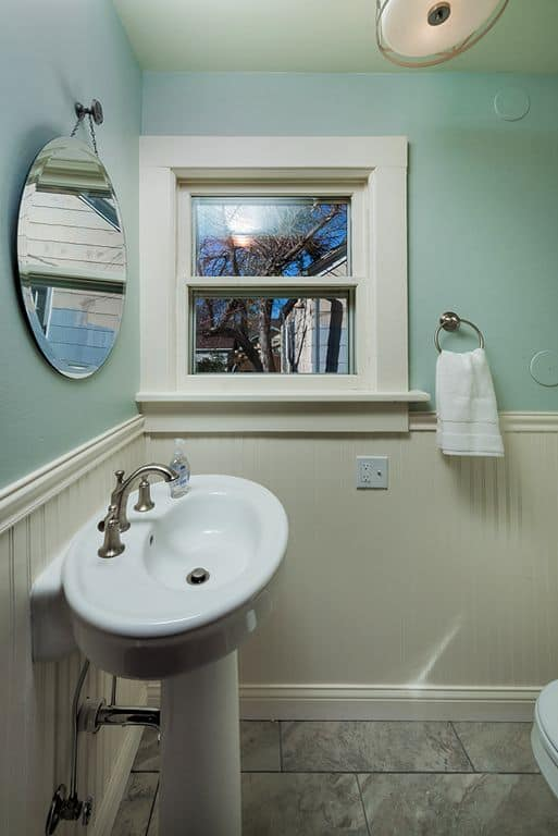 Farmhouse Powder Room With Wainscoting And High Ceiling.