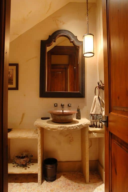 A wooden door opens to this farmhouse bathroom with vessel sink and a wooden framed mirror mounted beneath the vaulted wall.