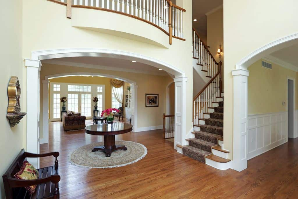 This foyer features a center table set on a rug. It also matches the seat in front of the classy staircase.