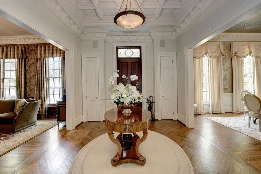 This foyer features a hardwood flooring surrounded by white walls lighted by a pendant light.