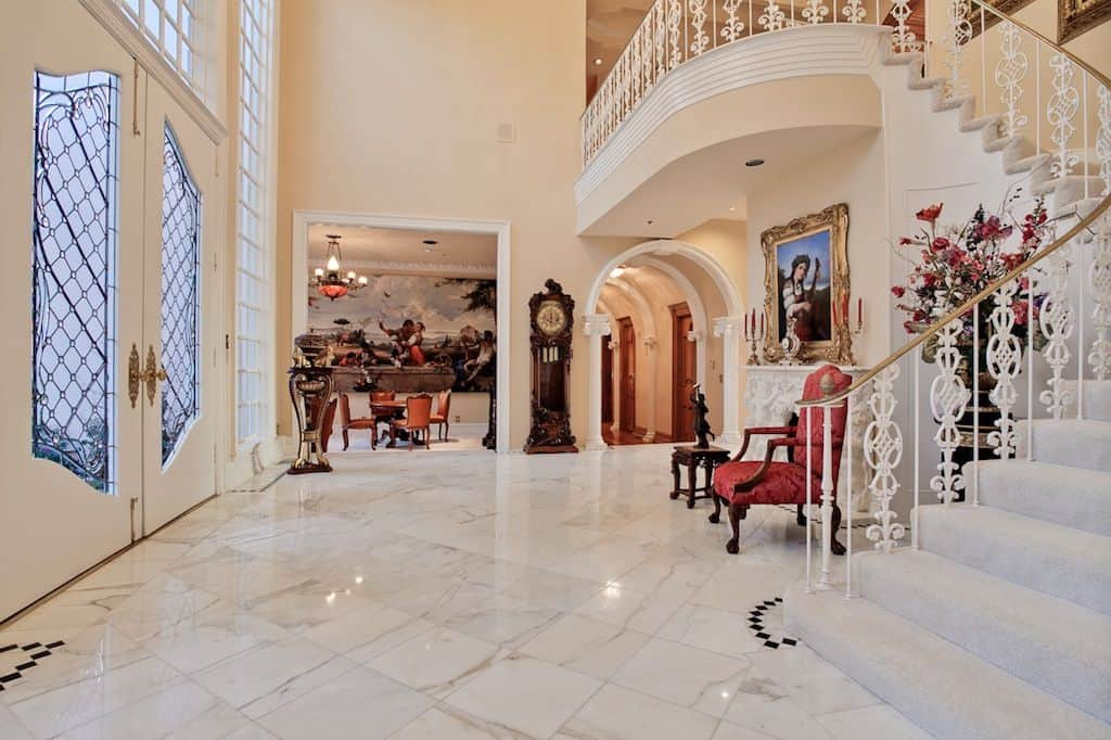 This elegant foyer boasts a marble tiles flooring reflecting the beautiful ceiling lights. The red chair near the fireplace looks very charming.