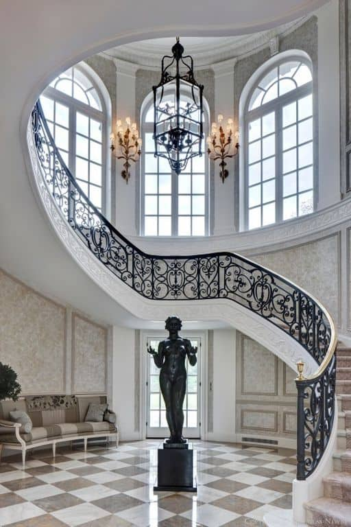 This elegant foyer boasts a statue set on the tiles flooring. The couch on the side perfectly fits with the gorgeous walls and staircase.