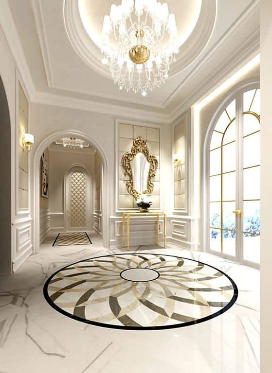 This elegant foyer boasts a stylish flooring, white walls added by classy gold-finished details and a grand chandelier.