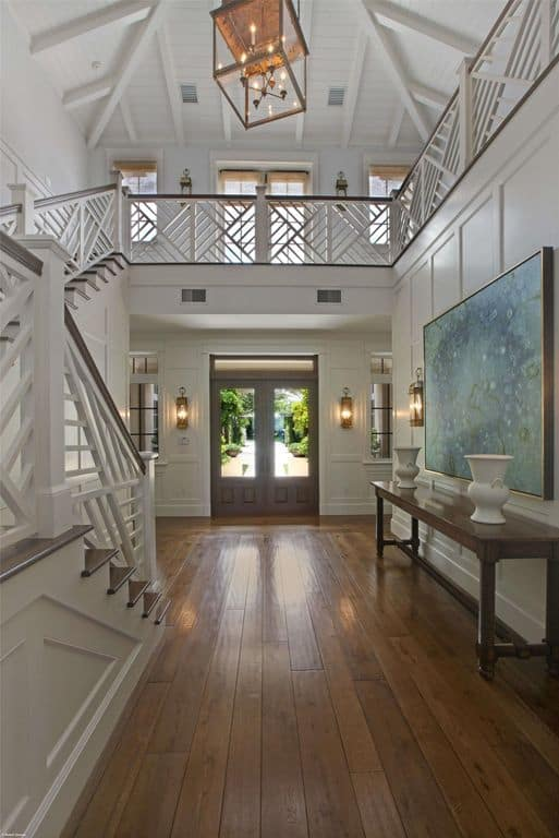 This foyer features a hardwood flooring and white walls. The beautiful chandelier set on a high ceiling looks stunning.