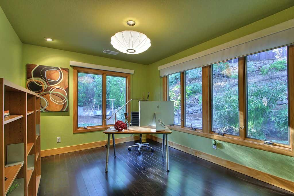 Fresh home office decorated with a round pendant light and lovely wall art mounted on the green wall. It includes a wooden bookcase and office desk paired with a black leather chair.