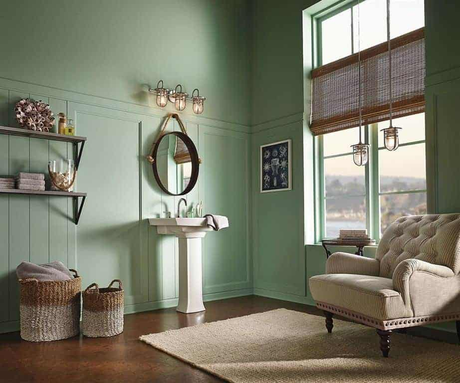 Mint green bathroom furnished with a brown tufted chair and wooden side table over a tan rug. It is lighted by glass pendants that match the sconces above an oval mirror and pedestal sink.