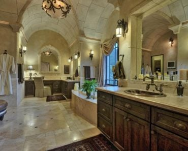 Large Traditional master bathroom with archway tile ceiling, wall sconces, drop-in tub and walk-in shower.