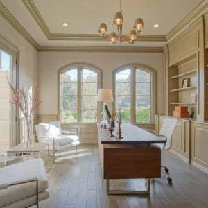 Home office with glass door and windows with chandelier.