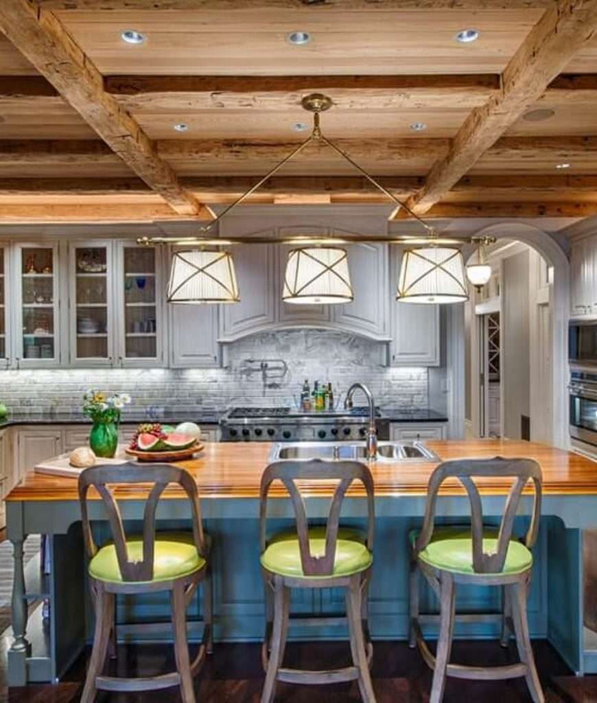 Southwestern kitchen with beam ceiling, gray tile backsplash and central island with a breakfast bar.
