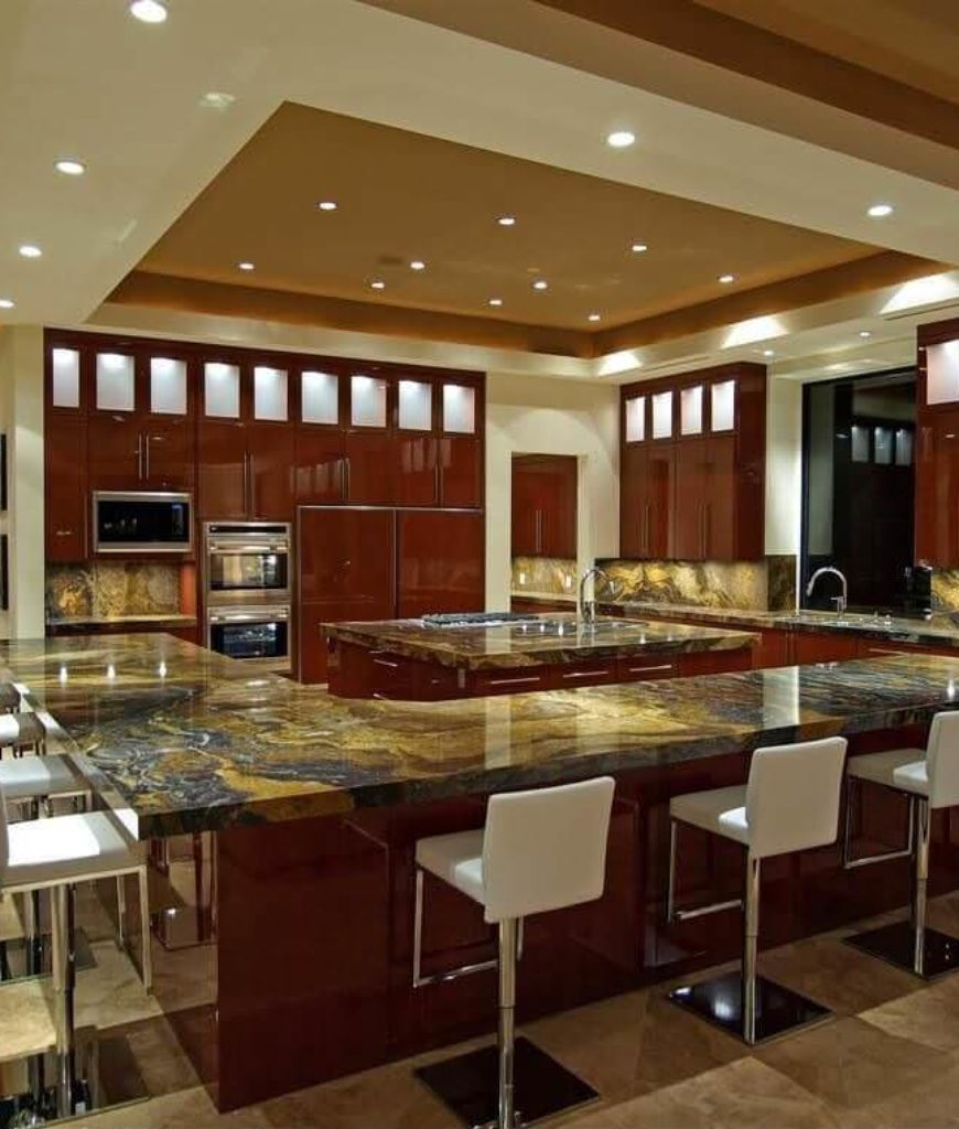 Massive modern kitchen with tray ceiling and marble backsplash, countertops and tile flooring.