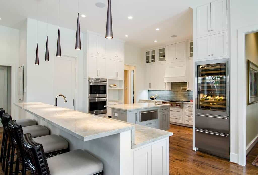 White kitchen with a hardwood flooring. The counters feature marble countertops. The narrow center island is lighted by stylish pendant lights.