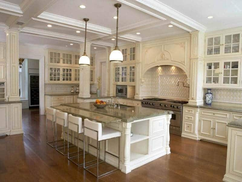 This kitchen offers classy cabinetry and kitchen counters along with a breakfast bar with modish bar stools set on the hardwood floors.