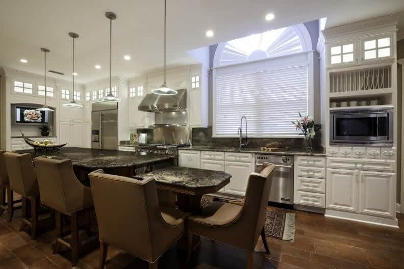 Contemporary kitchen with white cabinetry and a black marble breakfast island in two levels lined with brown leather chairs. It has wood plank flooring and an arched window covered with white blinds.