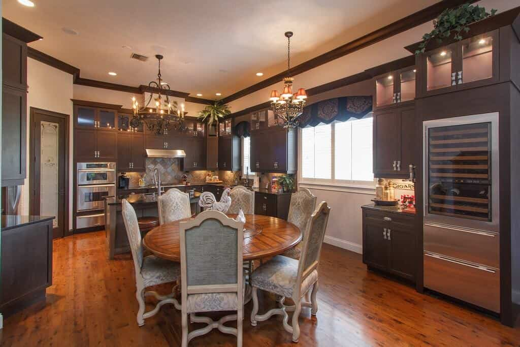 Traditional kitchen boasts dark wood cabinetry and a round dining table paired with lovely highback chairs and lighted by vintage chandeliers.