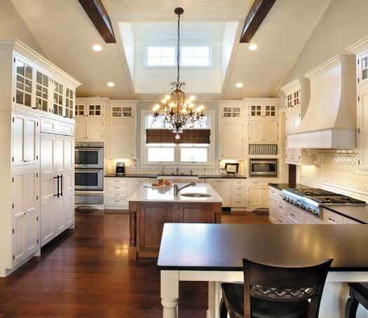 White kitchen featuring a large center island and a peninsula lighted by recessed lights and a chandelier.