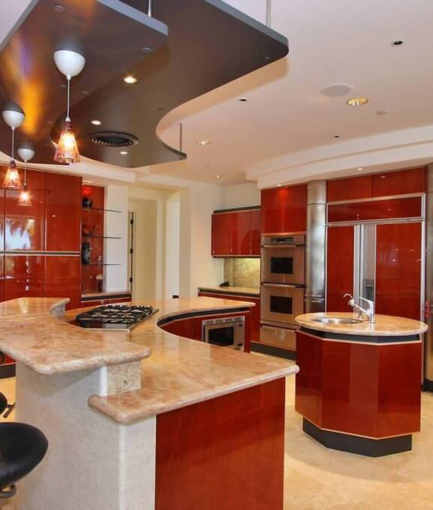 Red modern g-shape kitchen with flat panel cabinetry, stainless steel appliances and 2 islands.