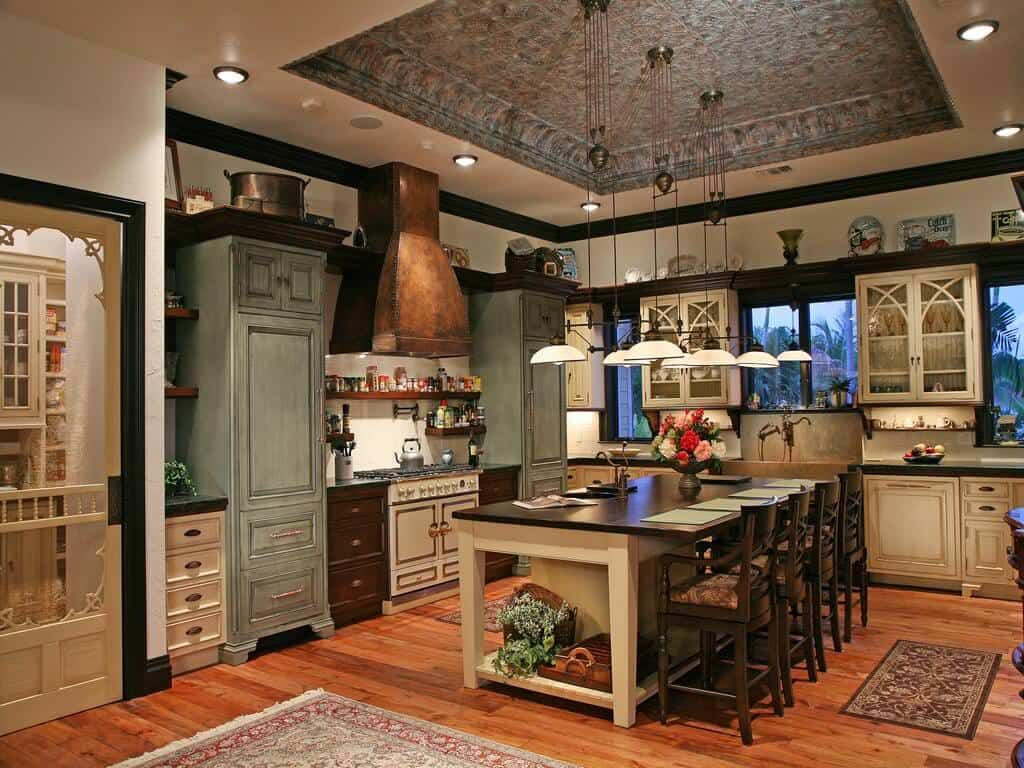 Country style kitchen with tray ceiling, pendant lights and hardwood flooring.