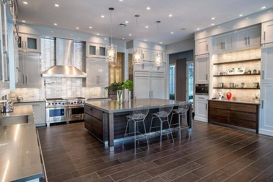 Large industrial kitchen featuring wooden tiles flooring, a large center island with a breakfast bar, lighted by pendant lights and built-in shelving.