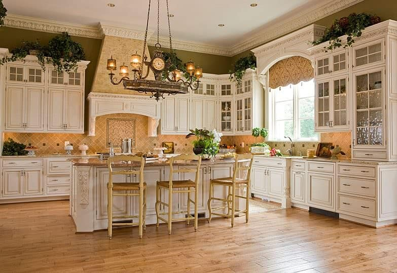 A country style kitchen with white cabinetry and breakfast island lighted by a vintage chandelier. It has wood plank flooring and moss green walls with ornate crown molding.