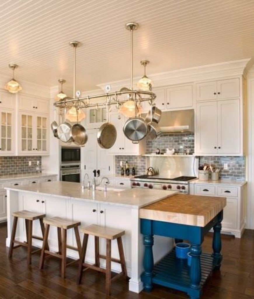 White kitchen with beam ceiling, pot rack and tile backsplash.