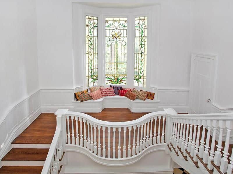 This home's second floor landing offers a bench seating with throw pillows near the gorgeous window.