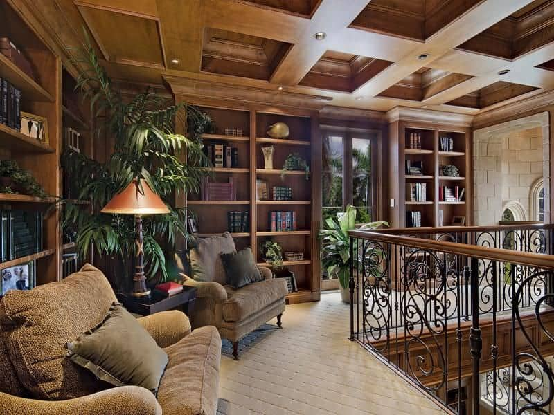 Traditional landing serving as the home's library. It features carpet flooring, cozy seats and a coffered ceiling.