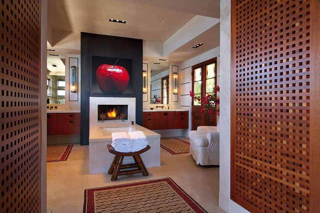 Contemporary primary bathroom featuring a bathtub with a fireplace that has an attractive wall decor on top of it.