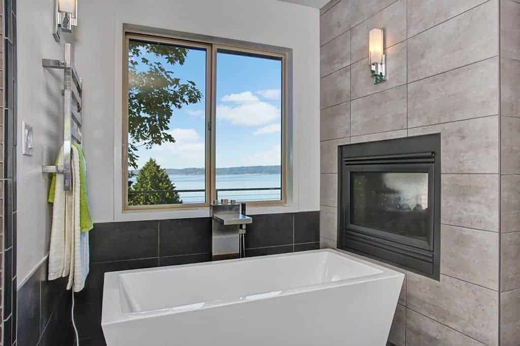 Contemporary primary bathroom with fireplace and freestanding tub.