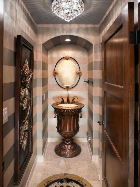 Mediterranean powder room with marble tiles and pedestal sink.
