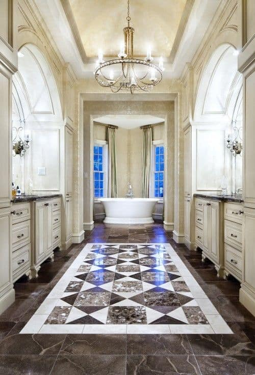 This elegant primary bathroom features a charming tiles flooring lighted by a beautiful chandelier. The hallway leads to the freestanding tub on the corner near the windows.