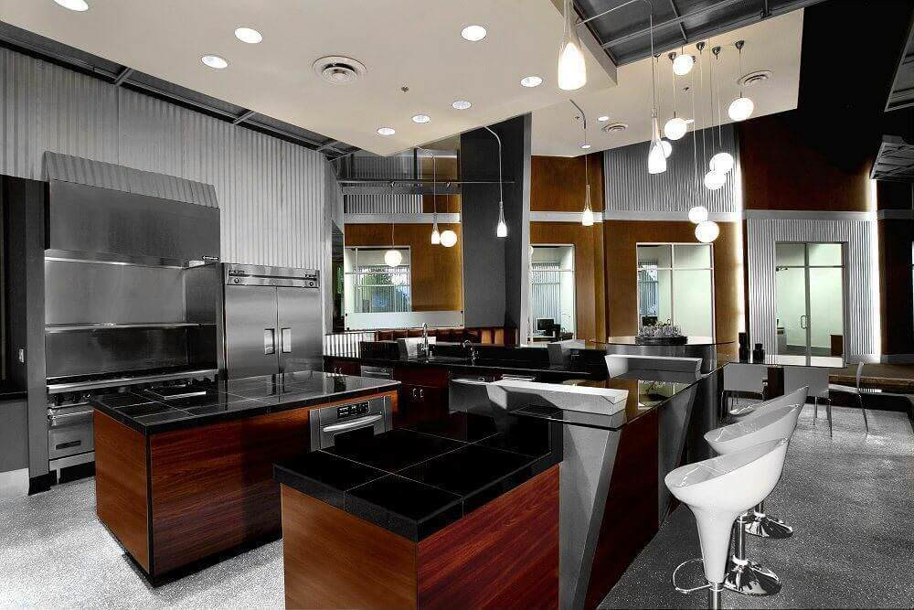 This kitchen features stylish black countertops on both kitchen counters and center island. It also offers a breakfast bar, multiple pendant lights and interesting gray carpet flooring.