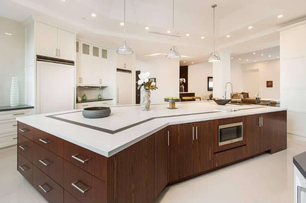 White modern kitchen featuring a gorgeous tray ceiling lighted by bright lights. The room also has a huge center island with a stylish countertop.