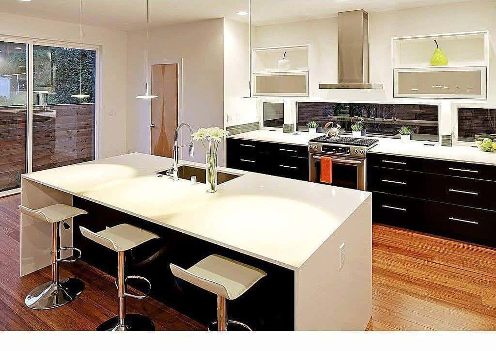 White modern kitchen featuring black kitchen counters and center island both with white countertops.