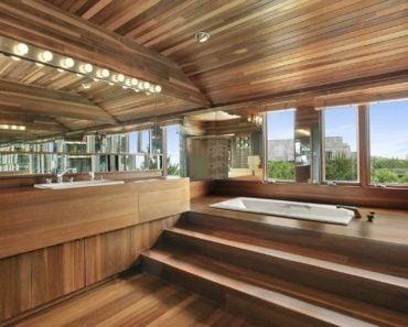 Modern master bathroom with beam ceiling, drop-in bathtub and hardwood floors.
