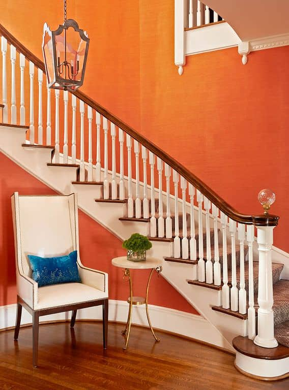 This foyer features orange walls with white details matching the chair beside the staircase.